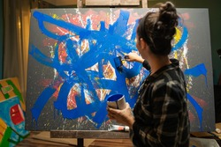 A woman stands against the canvas and I draw blue brush strokes painting the entire background of the painting. The girl holds a can of blue paint in her left hand and a brush in her right hand