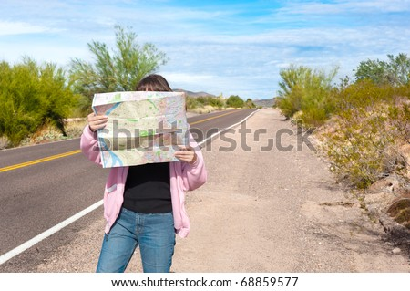 A woman stands along side a remote deserted road reading a map.