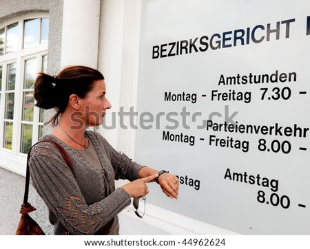 A woman stands before a closed office