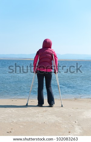 a woman stands on crutches at a lake shore, back view