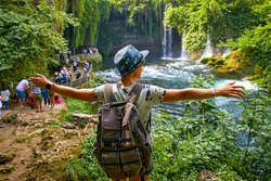 A woman stands with outstretched arms near a waterfall. Tourist with a backpack on the background of a waterfall and rainforest. The Upper Duden Waterfall