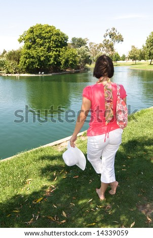 A woman strolls around a park lake in colorful springtime clothing.