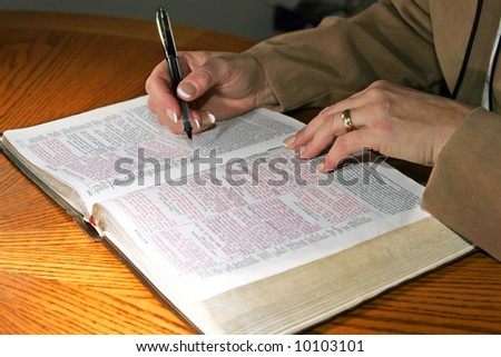 A woman studies a Holy Bible alone at a table (Christian image, shallow focus).