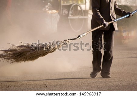 A woman sweeping a street (Xiahe, China)