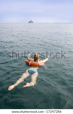 A woman swimming in the ocean with a lifebuoy