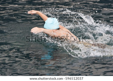 a woman swimming the butterfly stroke in a swimming pool #596512037