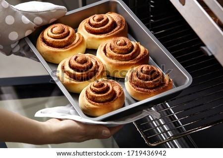 A woman takes out fresh buns from the oven. Cinnamon rolls are baked in the oven. Homemade baking.
