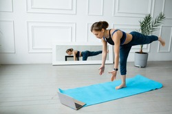 A woman takes yoga courses online on a laptop at home. Balance exercises. Stretching legs and arms to the floor