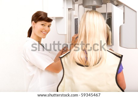 A woman taking a panoramic digital x-ray of a patients teeth