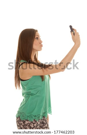 a woman taking a picture of her self with her phone to send.
