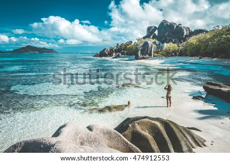 A woman taking pictures of the most beautiful beach of Seychelles - Anse Source D'Argent