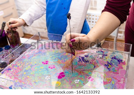 """A woman teacher shows a girl how to create a pattern of paints on the surface of the water using a special tool. Hands close up. Ebru Art, the Ancient Techniques of """"Painting on Water"""""""