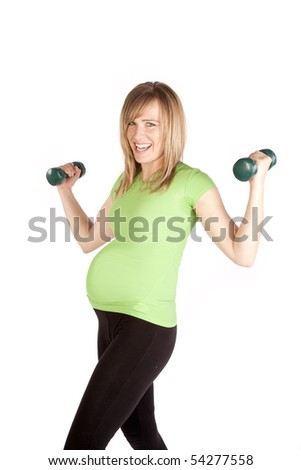 A woman that is pregnant is working out with weights.