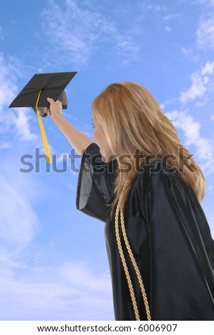 A woman throwing her graduation cap into the air