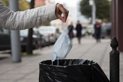 A woman throws a facemask at a public trash can on a city street. The hygiene mask goes to the trash bin.
