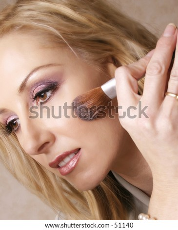 A woman touches up her makeup