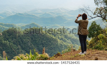 A Woman Tourist Is Taking Photo of Mountains and Hills with Her Mobile Phone / Smart Phone at The Scenic View Point of Mae Hong Son Province, Northern Thailand.
