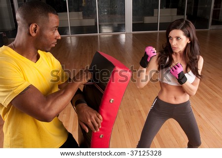 a woman trains with her trainer and is in a punching stance