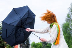 A woman tries to hold her umbrella in a strong wind