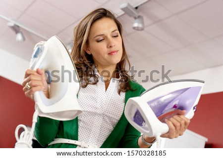 A woman trying to decide which iron to buy