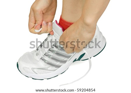 A woman tying a sport shoe; clipping path