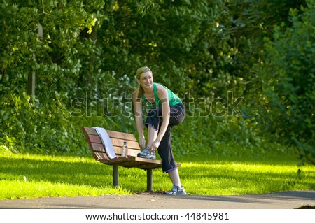 a woman tying her shoe laces on a bench in the park