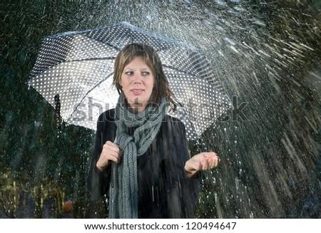 A woman under an umbrella during heavy rainfall