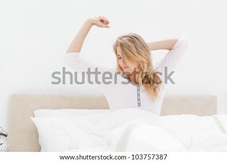 A woman upright in bed, one arm stretching  and the other behind her head which is turned to the side.