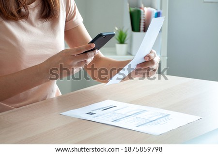 A woman uses a smartphone to scan the barcode to pay monthly phone bills after receiving an invoice sent to home. Online bill payment concept
