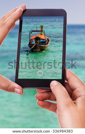 a woman using a smart phone to take a photo of a traditional thai long tail boat floating in a tropical sea