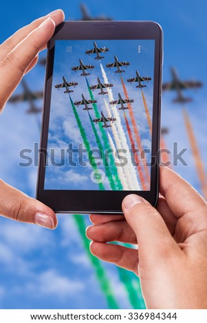 a woman using a smart phone to take a photo of an airshow performance