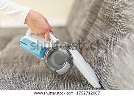 A woman vacuuming furniture in a house with a hand-held portable vacuum cleaner. Stockfoto ©