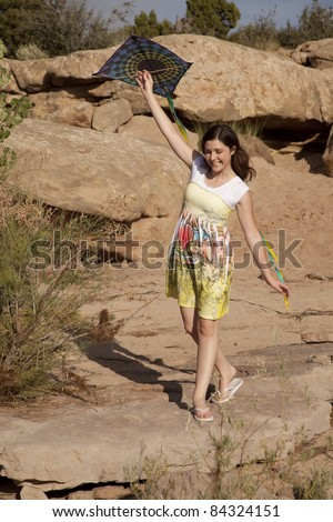 a woman walking along a rocky path with a smile on her face and her kite in her hands. - stock photo