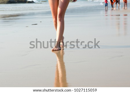 A woman walking along the beach on a Sunny day #1027115059