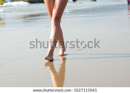 A woman walking along the beach on a Sunny day #1027115065