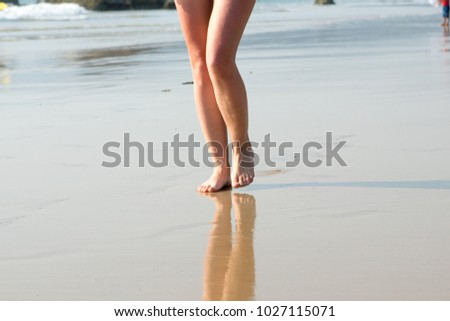 A woman walking along the beach on a Sunny day #1027115071