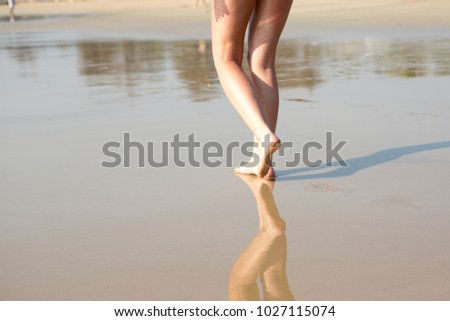 A woman walking along the beach on a Sunny day #1027115074