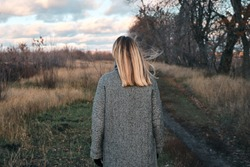 A woman walking in a field outdoors. Beautiful autumn landscape, fall foliage. Rural scenic sunset. Rest and recovery in the weekend. Stylish happiness  girl in comfortable clothes. Evening adventure