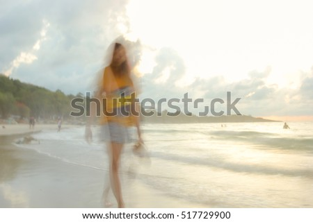 A woman walking on the beach at dawn. slow speed shutter