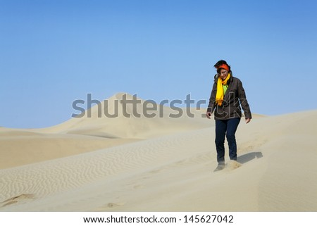 a woman walking on the dunes of the desert
