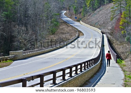 A woman walking on the path beside a highway.