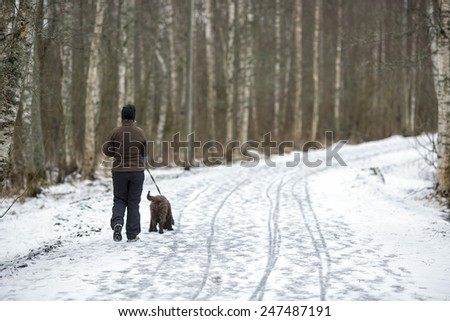 A woman walking the dog in the park.