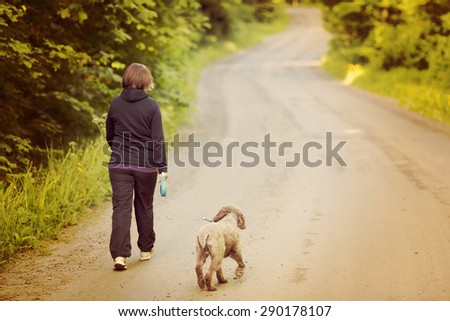 A woman walking the dog on a silent road. Image has a vintage effect. Dog breed is Lagotto romagnolo also known as Italian waterdog.