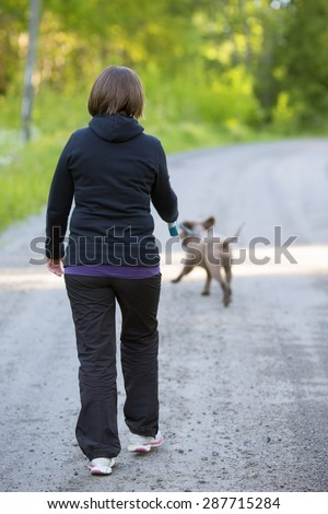 A woman walking the dog on an empty road. The dog is a Lagotto Romagnolo also known as Italian waterdog.
