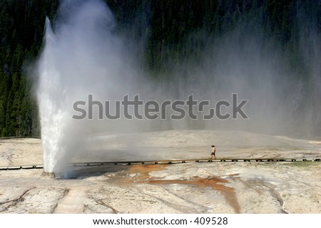 a woman walking towards the beehive geyser in yellowstone national park, wyoming.