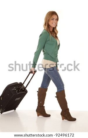 A woman walking with her luggage behind her with a smile on her face