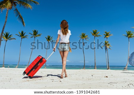 A woman walks along the beach with a red suitcase kind of travel fun palm model exotic exotic tropics summer #1391042681