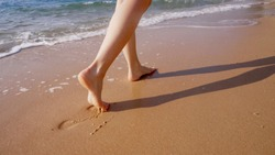 A woman walks along the golden sand of a beach. Female legs walk by the sea. Bare feet of a woman walking along a sandy shore with waves. Summer vacation or vacation.