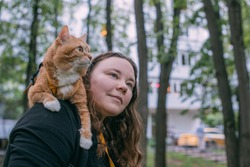 A woman walks in the park with a cat. The cat is sitting on his shoulder. Young girl on a walk in a green park near the house with a red curious cat
