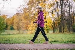 a woman walks on Scandinavian sticks in the Park. healthy lifestyle